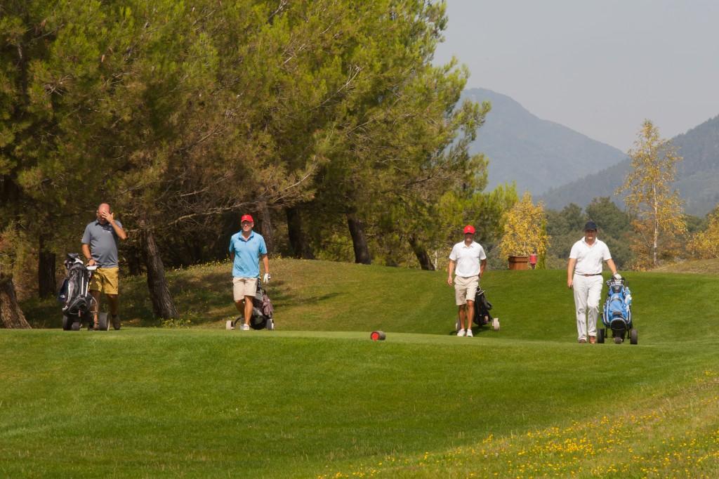 Golfistas caminan entre dos hoyos